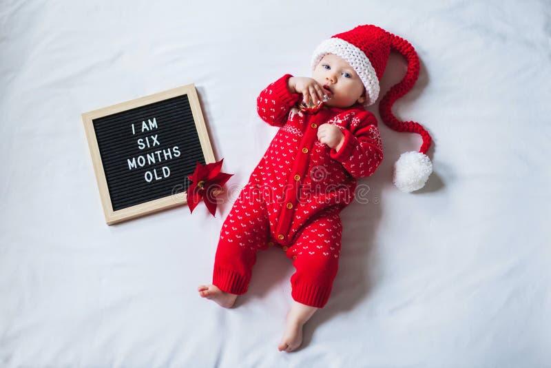 6 Sześciomiesięczne dziecko leżące na białym tle w kostiumie Świętego Mikołaja Skład płaski zdjęcia royalty free