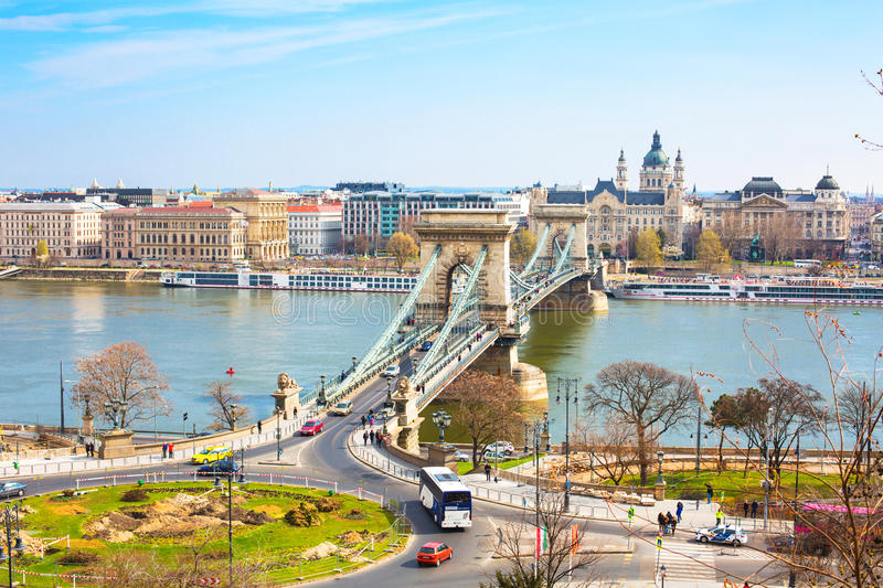 The Szechenyi Chain Bridge over Danube, Budapest. Landmark of Budapest, Szechenyi Chain Bridge that spans the River Danube between Buda and Pest. Buildings at royalty free stock photography