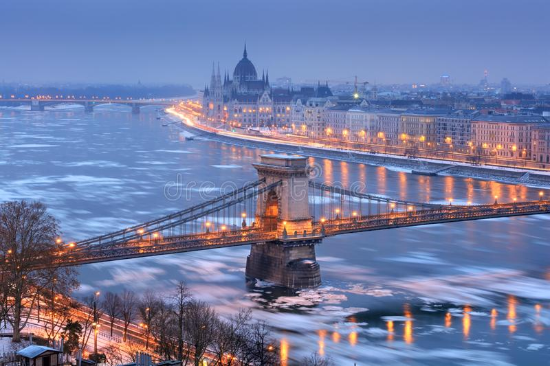 Szechenyi chain bridge and Budapest view in winter night. Szechenyi chain bridge and Pest riverfront with Parliament outline in winter night, Budapest royalty free stock images