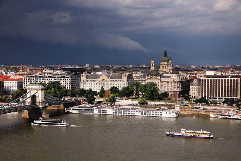 The famous Chain Bridge across the Danube river and a part of left bank of the Danube under storm clouds, seen from Gellert hill. stock photos