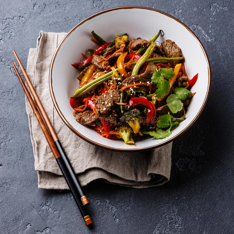 Szechuan beef stir fry with vegetables in bowl. On dark stone background stock photo