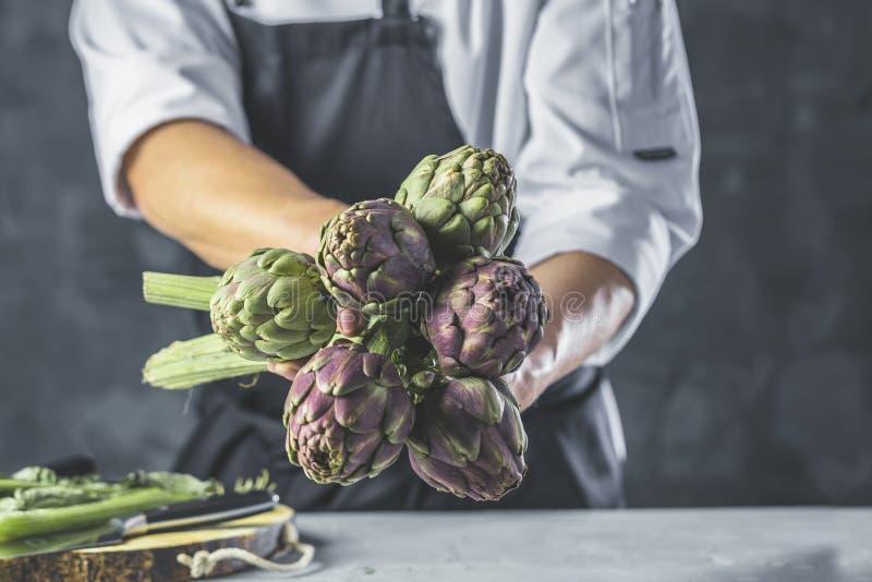 Szefów kuchni tnący karczochy dla obiadowego przygotowania - Obsługuje kucharstwo wśrodku restauracyjnej kuchni obraz royalty free
