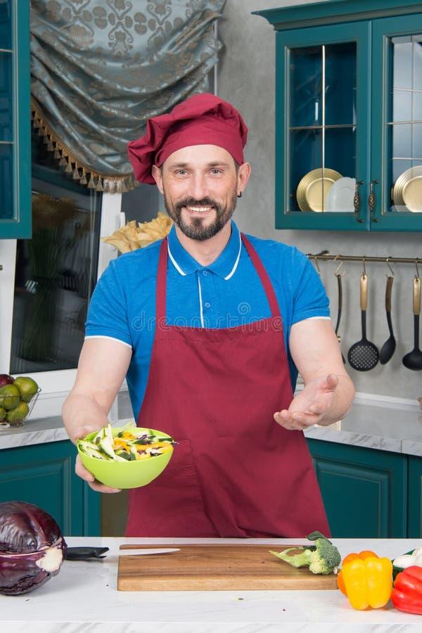 Szefów kuchni wellcomes z sałatką Facet w kapeluszowym chwyt zieleni talerzu z sałatką w rękach na kuchni zdjęcie stock