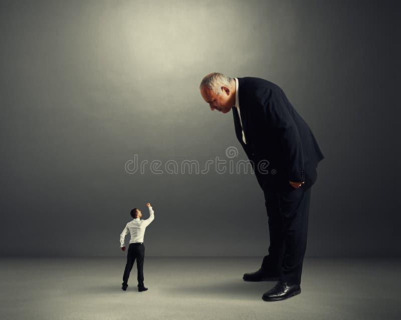 Szef dobry patrzejący małego pracownika zdjęcie stock