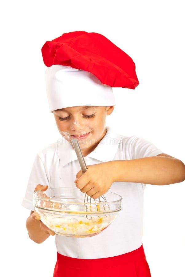 Szef kuchni chłopiec miesza ciasto zdjęcie royalty free