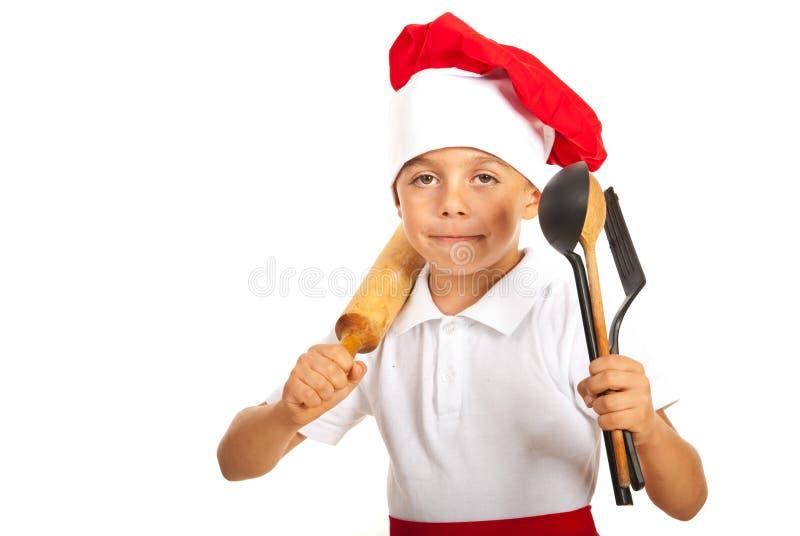 Szef kuchni chłopiec z wiele naczyniami obraz royalty free