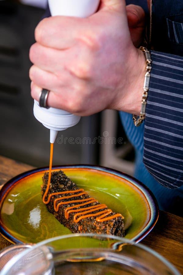 Szef kuchni dekoruje deser z czekoladowym gąbka tortem Mistrzowska klasa w kuchni Proces kucharstwo Krok obok zdjęcie royalty free