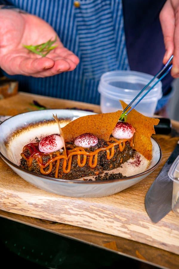 Szef kuchni dekoruje deser z czekoladowym gąbka tortem Mistrzowska klasa w kuchni Proces kucharstwo Krok obok obraz stock