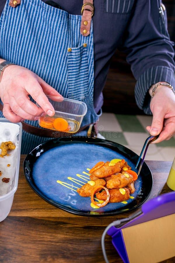 Szef kuchni dekoruje naczynie od uwędzonej sum głowy w cieście naleśnikowym Mistrzowska klasa w kuchni Proces kucharstwo Krok po  zdjęcie stock