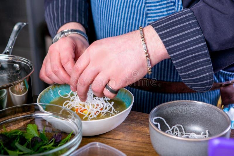 Szef kuchni dekoruje polewkę Fo Bo od uwędzonego suma z celofanowymi kluskami Mistrzowska klasa w kuchni Proces kucharstwo fotografia stock
