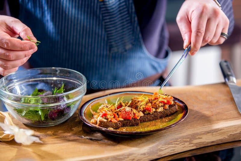 Szef kuchni dekoruje weganin kanapki z piec serem na smażącym rzemiosło chlebie i warzywami Mistrzowska klasa w kuchni _ fotografia royalty free