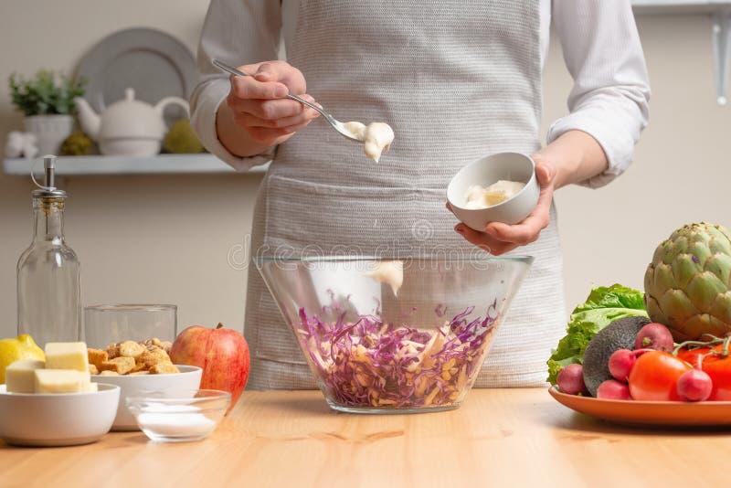 Szef kuchni dodaje majonez sałatka, fertanie, w trakcie jarskiej sałatki w domowej kuchni Lekki tło dla fotografia stock