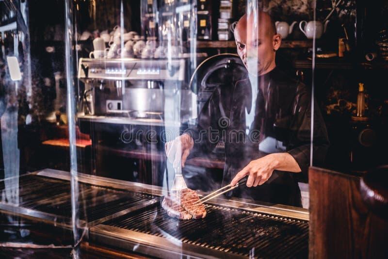 Szef kuchni gotuje wyśmienicie wołowina stek na kuchni, stoi za ochronnym szkłem w restauracji zdjęcia royalty free