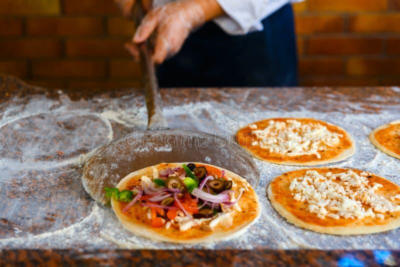 Szef kuchni iść stawiać pizzę w piekarniku zdjęcie royalty free