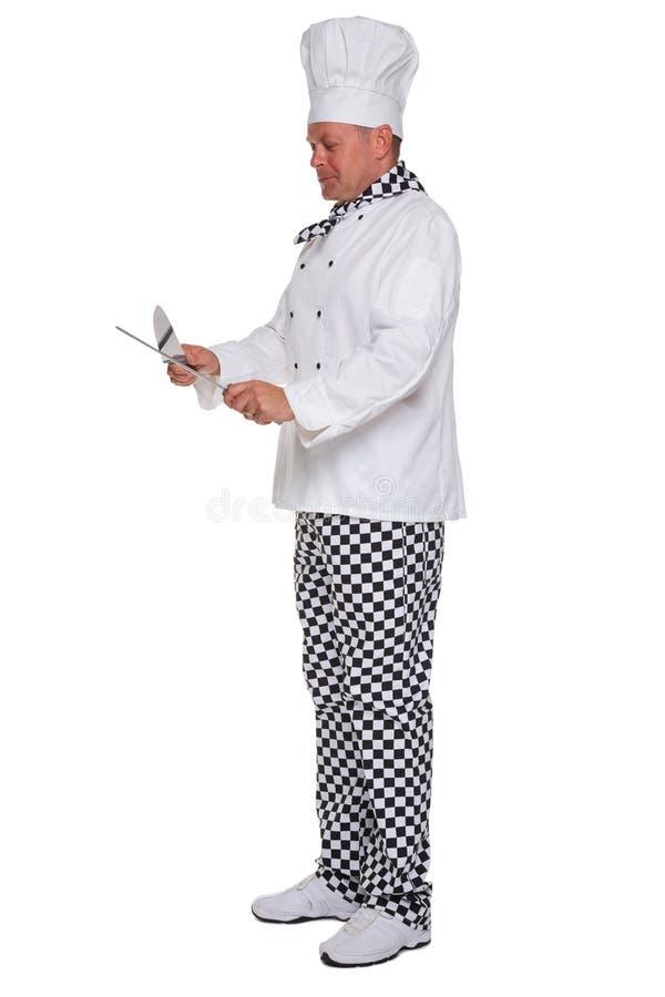 szef kuchni jego odosobniony nożowy ostrzenie obraz stock
