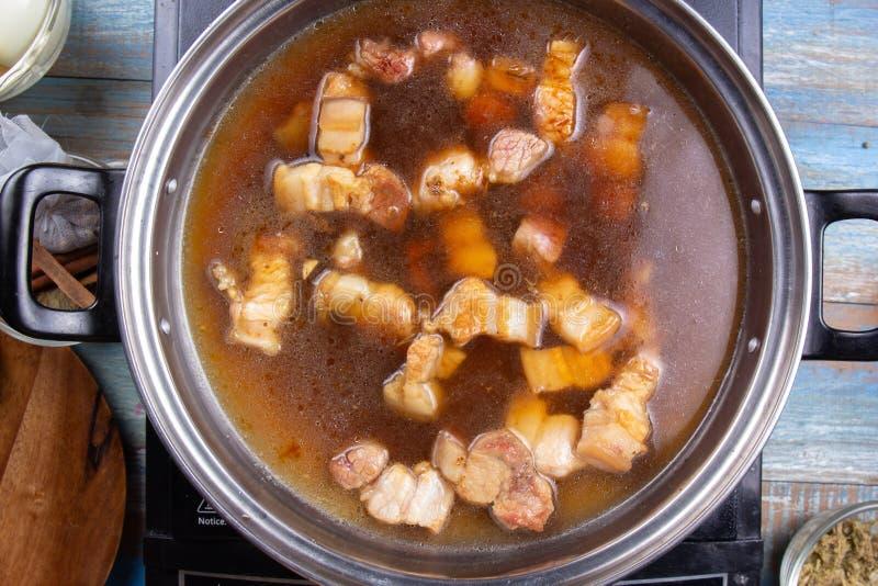 Szef kuchni k?adzenie gotuj?ca smugowata wieprzowina puszkowa? zdjęcie royalty free