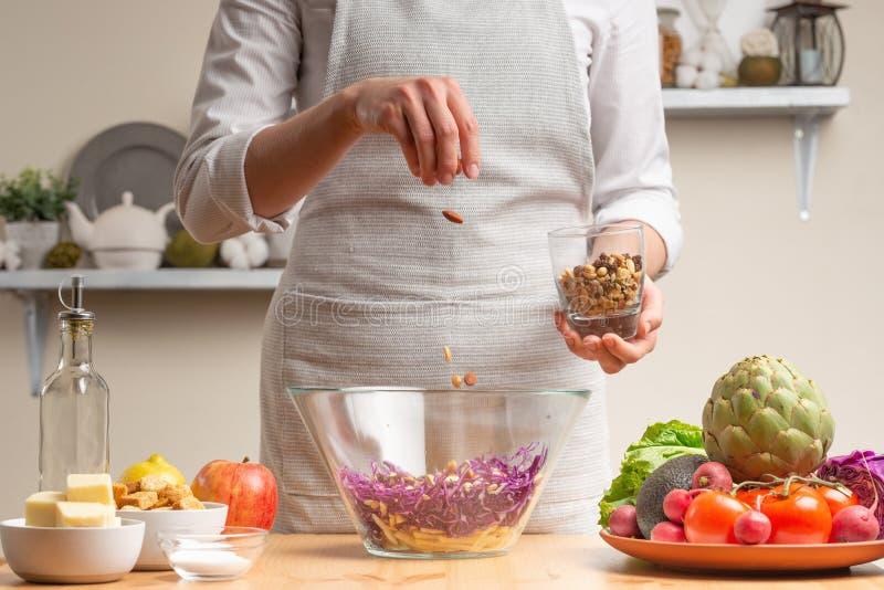 Szef kuchni kropi sałatki z dokrętkami, fertanie, w trakcie jarskiej sałatki z ręką szef kuchni w domowej kuchni ?wiat?o zdjęcia stock