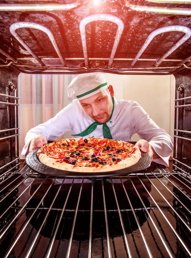 Szef kuchni kulinarna pizza w piekarniku fotografia royalty free