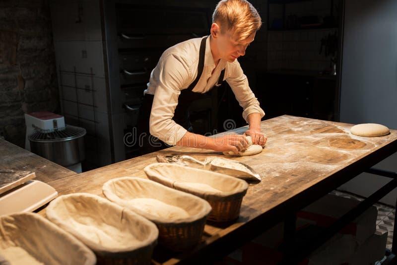 Szef kuchni lub piekarz robi ciastu przy piekarnią obrazy stock