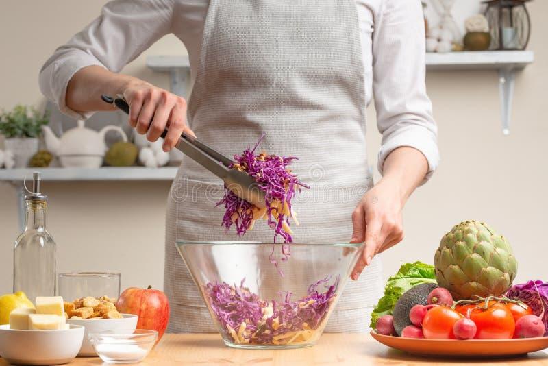 Szef kuchni miesza sałatki, fertanie, w trakcie jarskiej sałatki w domowej kuchni Lekki tło dla restauracyjnego menu fotografia stock