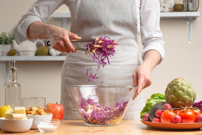 Szef kuchni miesza sałatki, fertanie, w trakcie jarskiej sałatki w domowej kuchni Lekki tło dla restauracyjnego menu obrazy royalty free