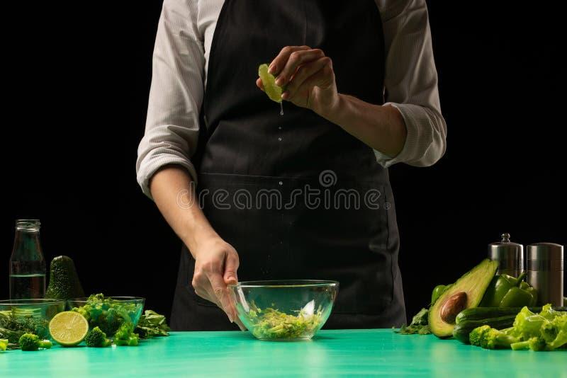 Szef kuchni na czarnym tła dolewania wapna soku na warzywach dla kulinarnych kucharstwo zieleni detoxification smoothies Zdrowy,  obrazy royalty free