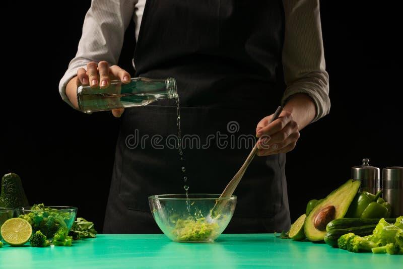 Szef kuchni na czarnym tle robi sokowi od warzyw z wodą dla przygotowania zielony detox smoothie Zdrowy, czysty zdjęcia stock