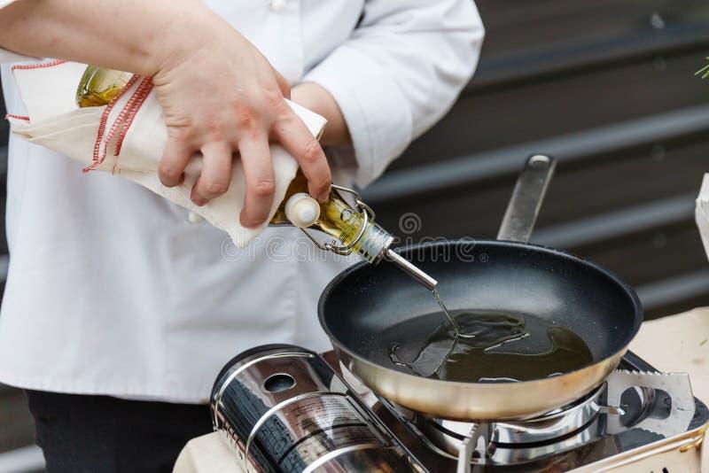 Szef kuchni Nalewa Rozmarynowego olej w niecce, Przygotowywającej Gotować obraz royalty free
