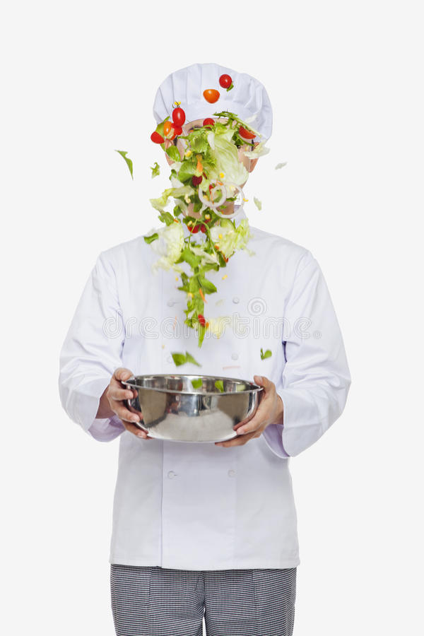Szef kuchni podrzuca sałatki, studio strzał obraz royalty free