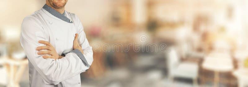 Szef kuchni pozycja w restauracji z krzyżować rękami sztandar obrazy stock