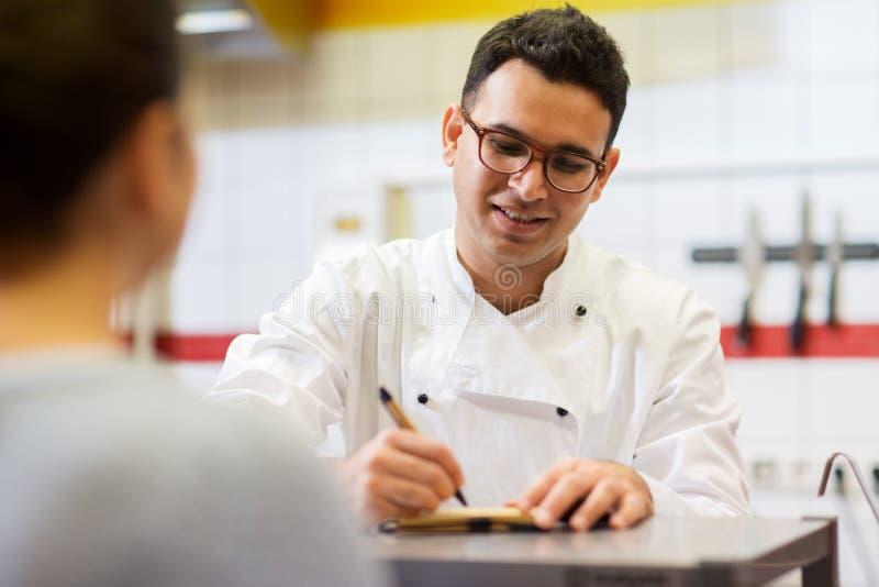 Szef kuchni przy fasta food writing restauracyjnym rozkazem fotografia stock
