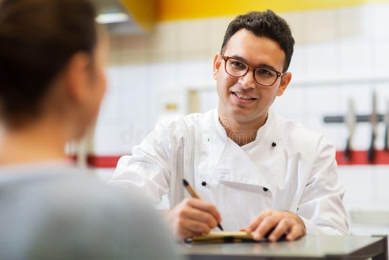 Szef kuchni przy fasta food writing restauracyjnym rozkazem obrazy royalty free
