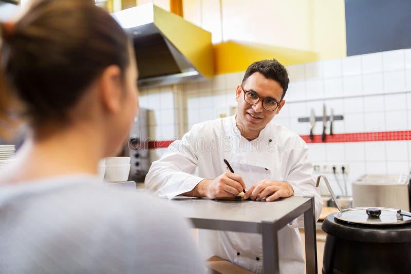 Szef kuchni przy fasta food writing restauracyjnym rozkazem zdjęcie stock