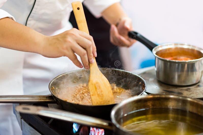 Szef kuchni przygotowuje jedzenie w kuchni, kucharz kuchni zdjęcia royalty free