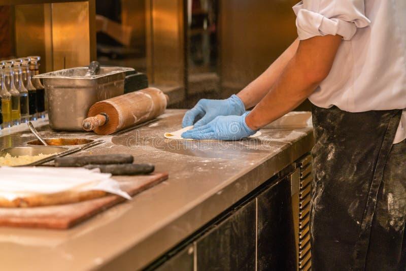 Szef kuchni ręka robi pizzy w kuchni zdjęcie stock