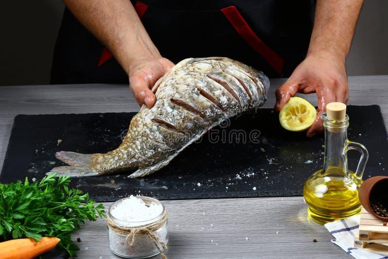 Szef kuchni ręki gotuje Świeżą rzekę łowią z cytrusa i warzywa składnikami na iłołupek desce, kulinarny karmowy pojęcie Autentycz fotografia stock
