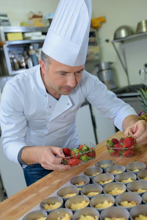 Szef kuchni robi truskawkowym tarts fotografia royalty free