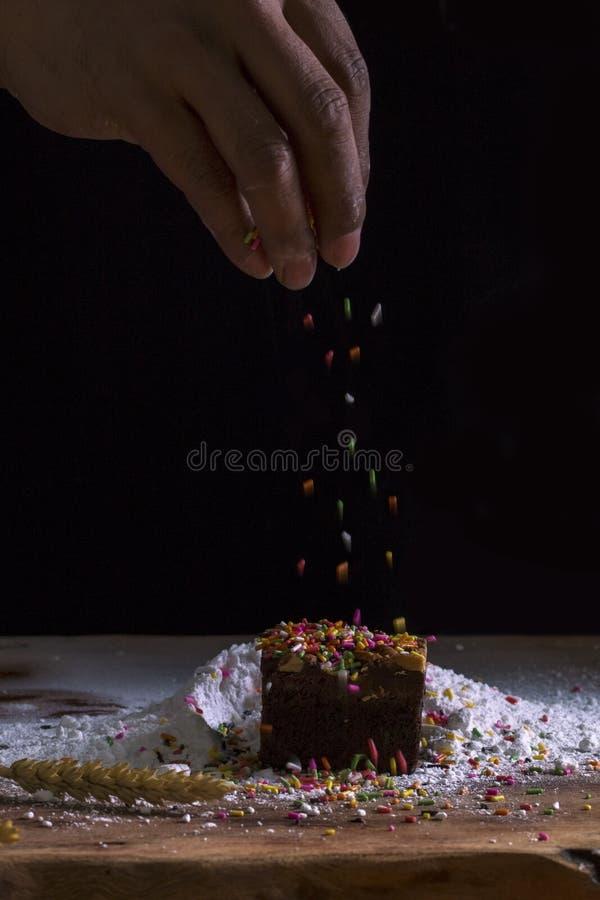 Szef kuchni s wręcza tryskaczowego czekoladowego punkt z koloru lodowaceniem fotografia royalty free