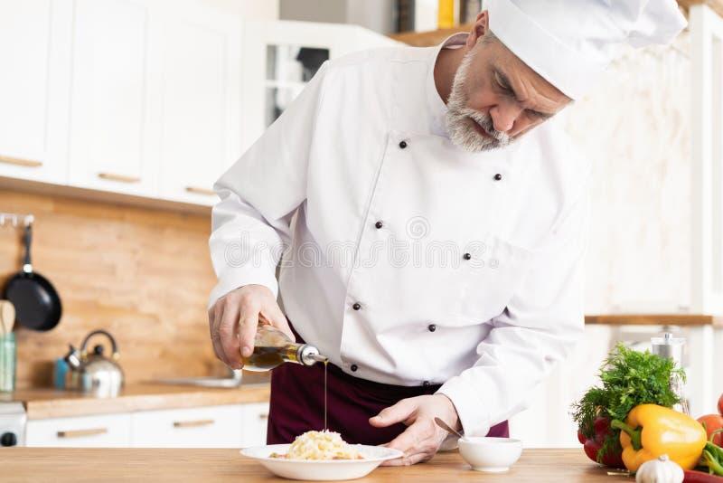 Szef kuchni uciera ser talerz z ?wie?ym makaronem obrazy stock