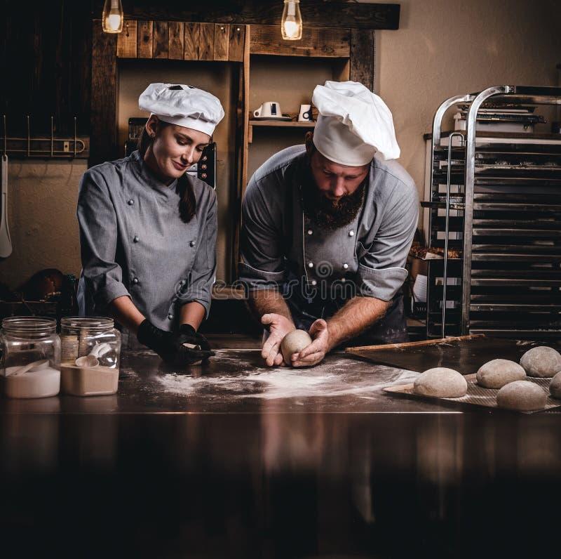 Szef kuchni uczy jego asystenta piec chleb w piekarni zdjęcie stock