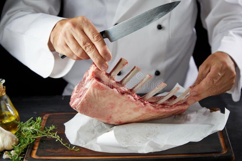 Szef kuchni w białego żakieta tnącym jagnięcym mięsie obrazy royalty free