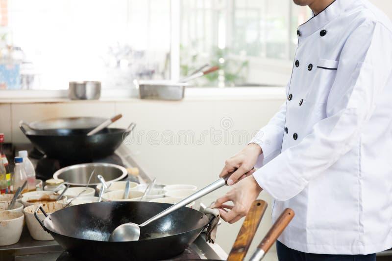 Szef kuchni w hotelowym lub restauracyjnym kuchennym ruchliwie kucharstwie obrazy stock