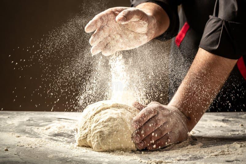 Szef kuchni wręcza kulinarnego ciasto na ciemnym drewnianym tle Białej mąki latanie w powietrze szef kuchni pojęcia karmowa śwież obrazy royalty free