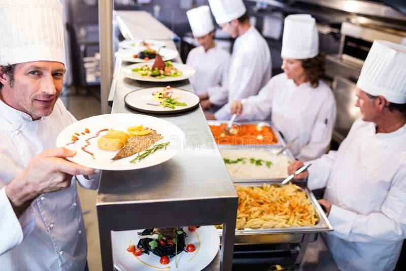 Szef kuchni wręcza obiadowych talerze przez rozkaz staci obraz royalty free