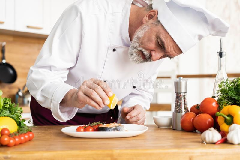 Szef kuchni z pilno?ci apretury naczyniem na talerzu, ryba z warzywami fotografia royalty free