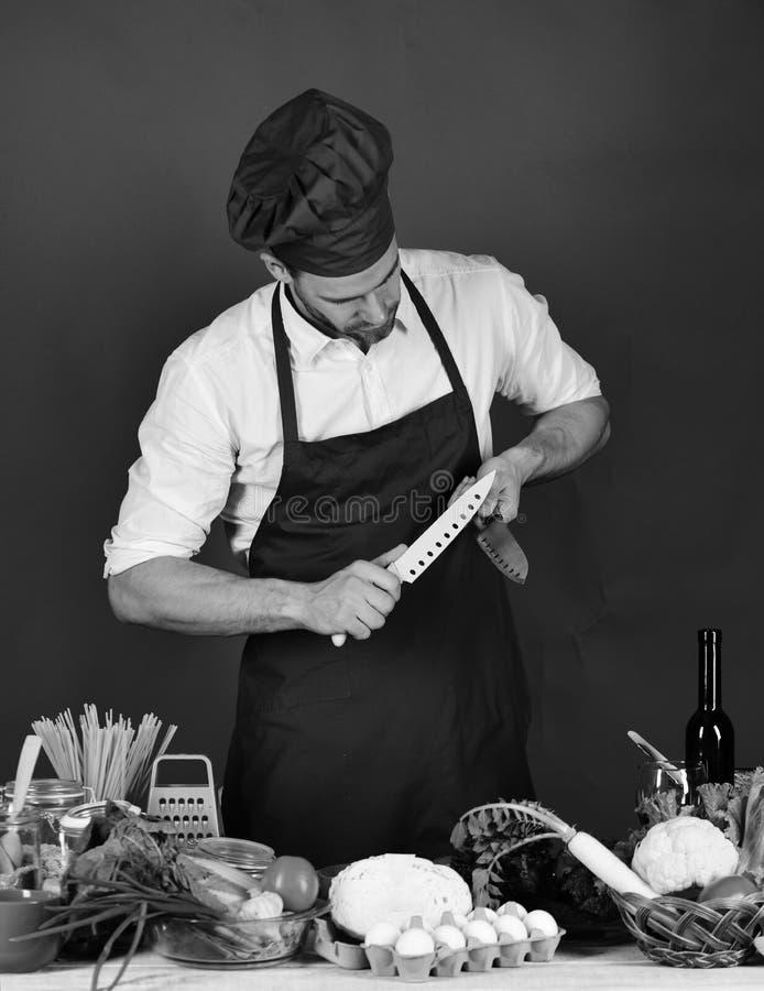 Szef kuchni z ruchliwie twarzą trzyma błękita i metalu noże na ciemnozielonym tle Mężczyzna w kucbarskim kapeluszu i fartuchu ost zdjęcie royalty free
