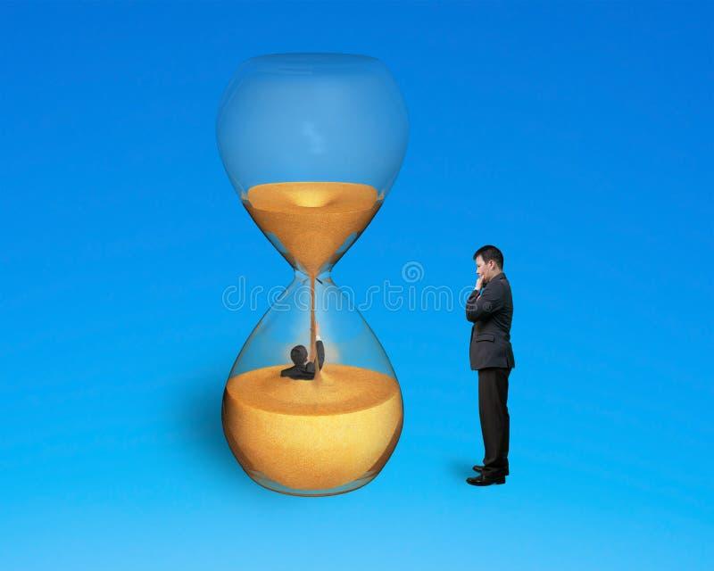 Szef nadzoruje pracownika zalewającego w hourglass zdjęcie stock