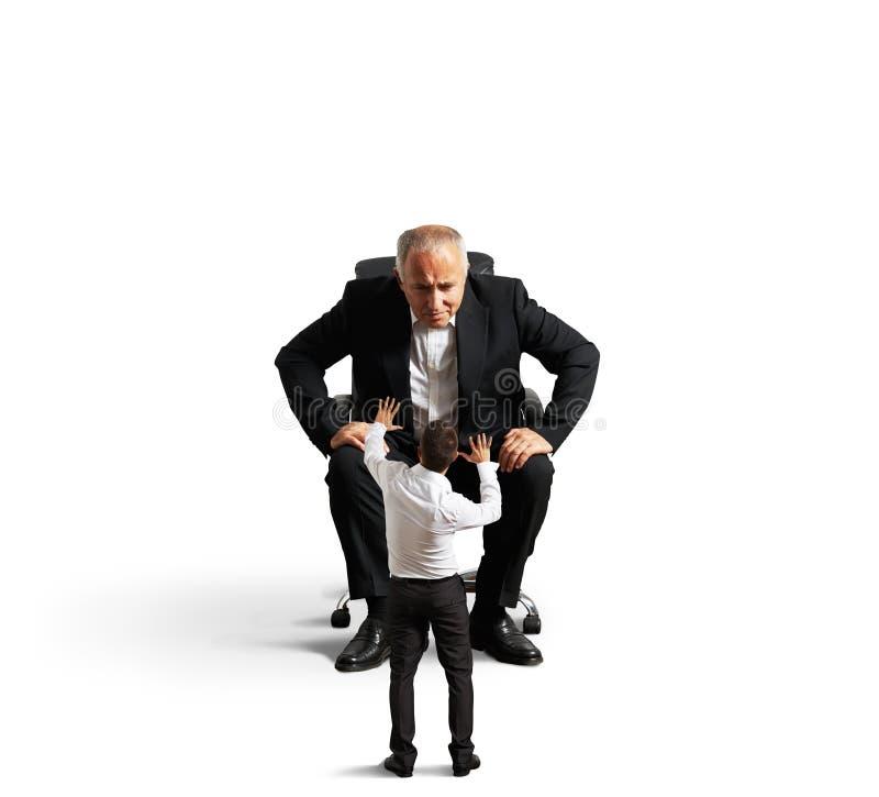 Szef patrzeje małego okaleczającego pracownika zdjęcia royalty free