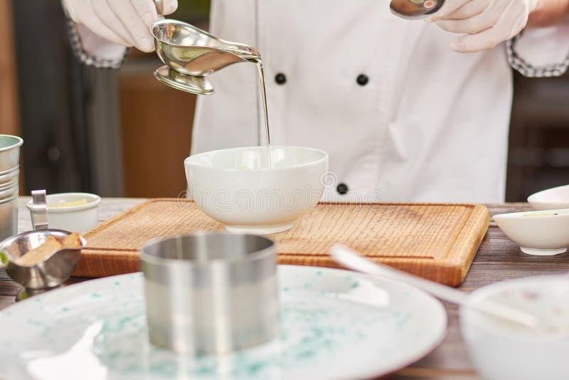 Szefa kuchni dolewania olej w białym pucharze zdjęcie royalty free