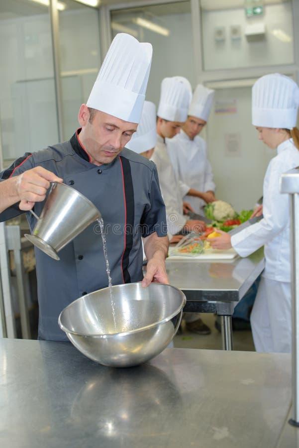 Szefa kuchni dolewanie w stal nierdzewna puchar obrazy royalty free